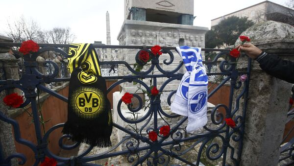 A man places a flower next to German football club scarves at the Obelisk of Theodosius, the scene of the suicide bomb attack, at Sultanahmet square in Istanbul, Turkey - Sputnik International