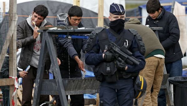 A French riot police officer (CRS) stands guard as migrants brush their teeth in a makeshift camp in what is known as the Jungle, a squalid sprawling camp in Calais, northern France, January 11, 2016. - Sputnik International