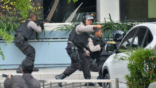 Indonesian police take position and aim their weapons as they pursue suspects outside a cafe after a series of blasts hit the Indonesia capital Jakarta on January 14, 2016 - Sputnik International