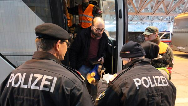 Austrian police officer check the identification documents of migrants before allowing them to get out a bus from Slovenia to cross the border from Slovenia into Austria, at a checkpoint at the Karawanks tunnel near Villach, Austria, Wednesday, Jan. 13, 2016. - Sputnik International