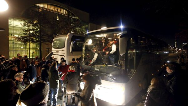 A bus (R) with refugees from the Bavarian town of Landshut is pictured after its arrival to the Chancellery building in Berlin, Germany, January 14, 2016 - Sputnik International