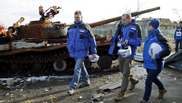 Deputy Chief of the Special Monitoring Mission of the Organization for Security and Cooperation in Europe (OSCE) to Ukraine Alexander Hug (L), with members of the mission, walks past a burnt tank as he inspects an area between self-proclaimed Donetsk People's Republic forces and Ukrainian government troops in the village of Kominternove north-east of the port city of Mariupol, Ukraine, January 15, 2016 - Sputnik International