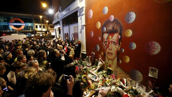 Fans stand by floral tributes at a mural of David Bowie in Brixton, south London, Britain January 11, 2016 - Sputnik International