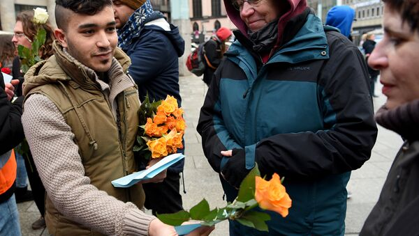 Refugees from Syria present flowers to passers-by as they demonstrate against violence near the Cologne main train station in Cologne, western Germany on January 16, 2016, where hundreds of women were groped and robbed in a throng of mostly Arab and North African men during New Year's festivities - Sputnik International