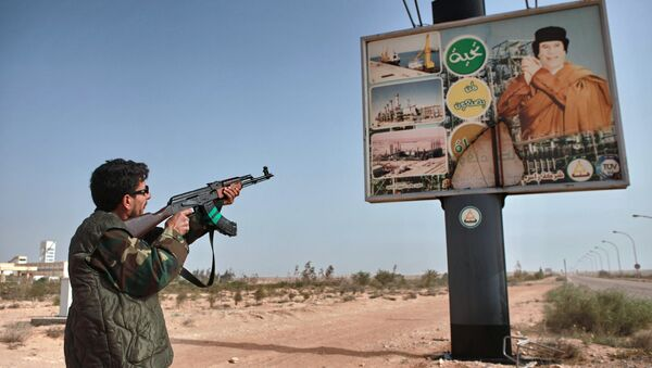 An armed supporter of the Libyan opposition shoots a machine gun at a poster with the image of Muhammar Gaddafi in the captured rebel town of Ras-Lanuf in the east of the country - Sputnik International