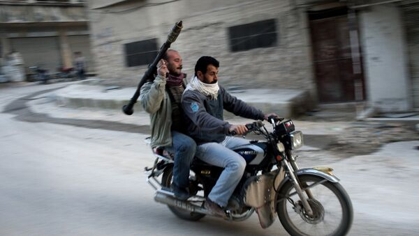 Supporters of the Free Syrian Army ride a motorcycle with a rocket-propelled grenade in Kafar Taharim, Syria. - Sputnik International