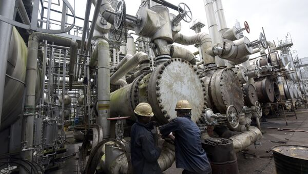 A picture taken on September 16, 2015 shows workers trying to tie a pipe of the first refinery in Nigeria, which was built in 1965 in oil rich Port Harcourt, Rivers State - Sputnik International