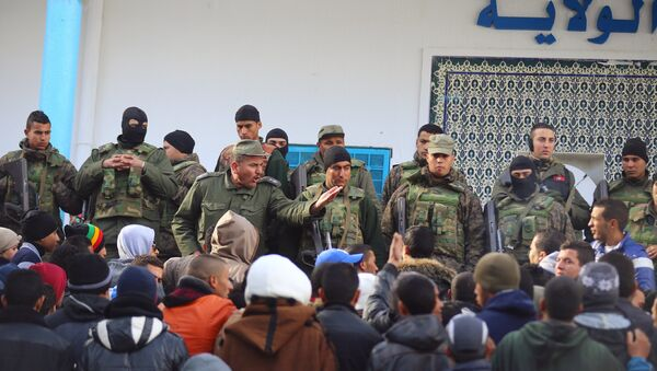 An army soldier tries to disperse protesters as he stands guard with his comrades outside the local government office during a protest in Kasserine, Tunisia January 22, 2016. - Sputnik International