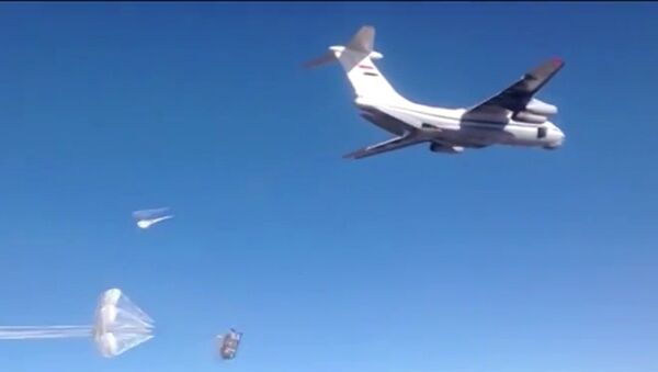 Syrian Air Force aircraft dropping humanitarian cargo on Russian parachute platforms in the area of Deir ez-Zor, Syria. - Sputnik International