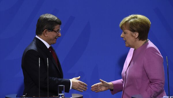 German Chancellor Angela Merkel (R) and Turkish Prime Minister Ahmet Davutoglu (L) shake hands during the press conference, after a meeting at the Chancellery, in Berlin on January 22, 2016 - Sputnik International