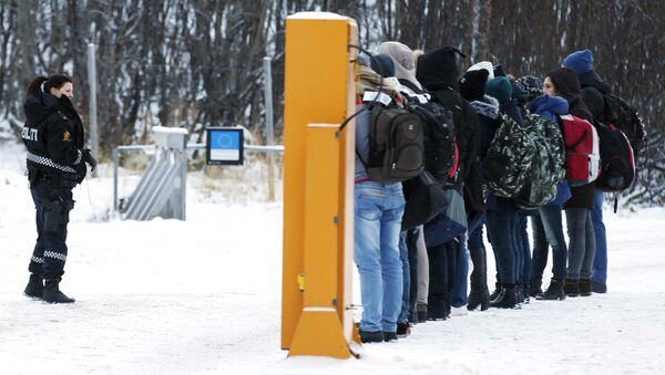 Migrants receive instructions from a Norwegian police officer at Storskog boarder crossing station near Kirkenes, after crossing the boarder between Norway and Russia on November 16, 2015 - Sputnik International