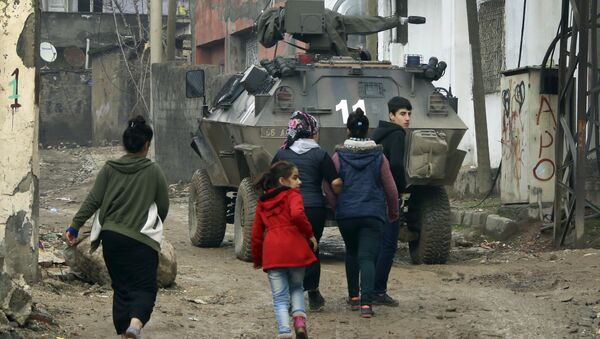 Backdropped by a Turkish forces armoured personnel carrier, residents walk around after the 24-hour curfew was lifted, in the mostly-Kurdish town of Silopi, in southeastern Turkey, near the border with Iraq, Tuesday, Jan. 19, 2016 - Sputnik International