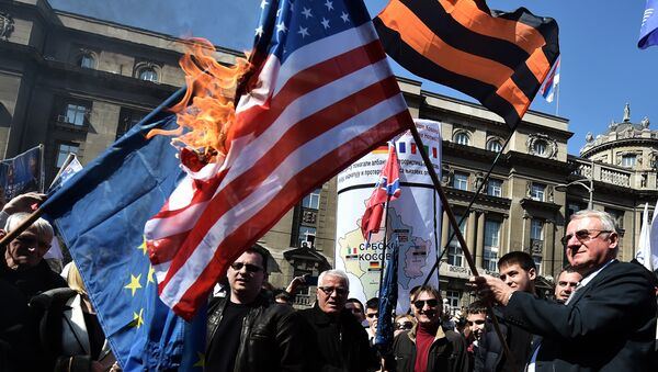 Serbian nationalist politician Vojislav Seselj (R) surrounded by his supporters holds a burning NATO flag during an anti-government rally on March 24, 2015, in front of the building of the former federal Interior Ministry in Belgrade - Sputnik International