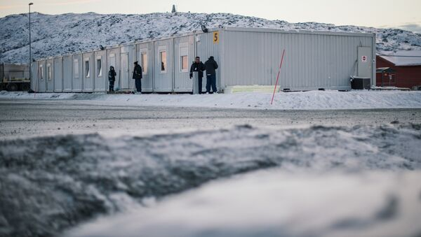 Refugees stand in front of residential containers at the arrival centre for refugees near the town on Kirkenes - Sputnik International