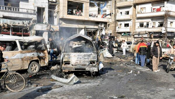 People inspect the site of a double bomb attack in the government-controlled city of Homs, Syria, in this handout picture provided by SANA on January 26, 2016 - Sputnik International