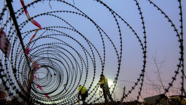 In this file photo workers take measurements of a near finished section of a 3,7 km long fence at a border crossing between Austria and Slovenia at Spielfeld, Austria on December 9, 2015. - Sputnik International