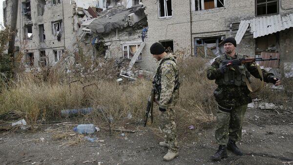 Ukrainian servicemen walks in the yard of a destroyed building in the Pisky village near Donetsk on October 26, 2015 - Sputnik International