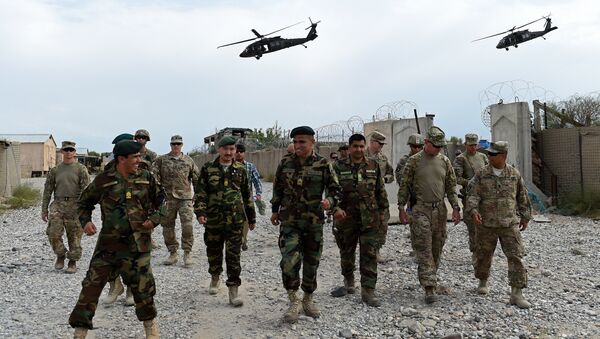 US army and Afghan National Army (ANA) soldiers walk as a NATO helicopter flies overhead - Sputnik International