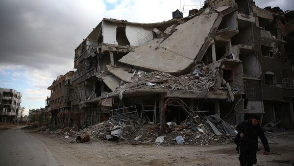 A photographer walks in the neighbourhood of Jobar, on the eastern outskirts of the capital Damascus, on January 23, 2016 - Sputnik International