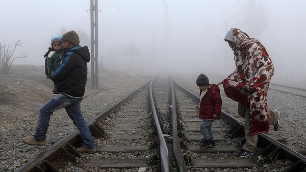 Migrants cross the railway tracks as they wait to cross the Greek-Macedonian border near the village of Idomeni, Greece, January 28, 2016 - Sputnik International