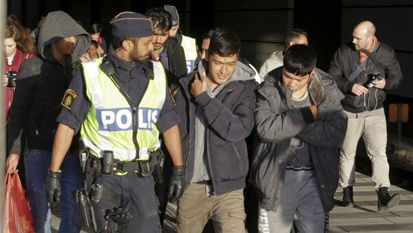 A group of migrants off an incoming train walk down a platform as they are accompanied by the police at the Swedish end of the bridge between Sweden and Denmark near Malmoe on November 12, 2015 - Sputnik International