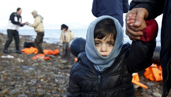 A Syrian refugee child looks on, moments after arriving on a raft with other Syrian refugees on a beach on the Greek island of Lesbos, January 4, 2016. - Sputnik International