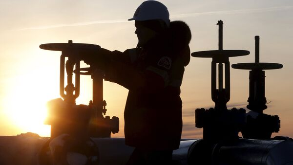 A worker checks the valve of an oil pipe at the Lukoil company owned Imilorskoye oil field outside the West Siberian city of Kogalym, Russia, January 25, 2016 - Sputnik International