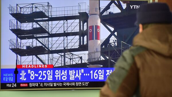 A man watches a news report on North Korea's planned rocket launch as the television screen shows file footage of North Korea's Unha-3 rocket which launched in 2012, at a railway station in Seoul on February 3, 2016 - Sputnik International