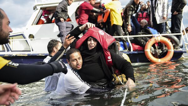 Migrant families - helped by rescuers - disembark on the Greek island of Lesbos after crossing with other migrants and refugees the Aegean Sea from Turkey, on November 25, 2015. - Sputnik International