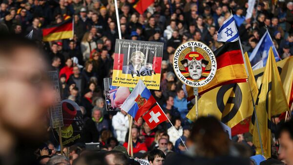Supporters of the anti-Islam movement Patriotic Europeans Against the Islamisation of the West (PEGIDA) hold posters depicting German Chancellor Angela Merkel during a demonstration in Dresden, Germany - Sputnik International