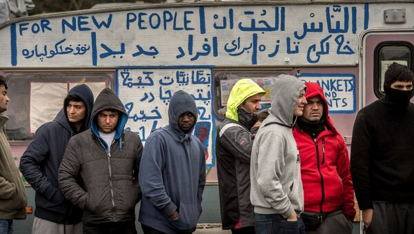 Refugees stand in the so-called Jungle migrant camp in Calais, northern France - Sputnik International