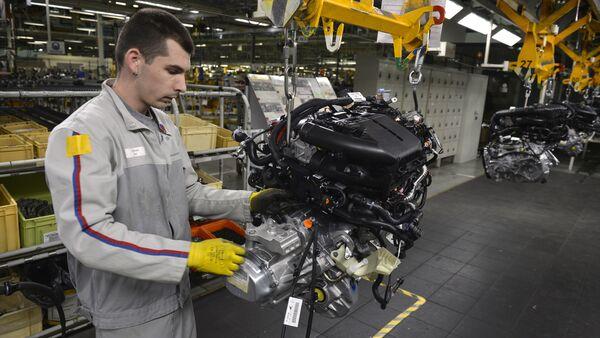 An employee works on the engine assembly line of the Peugeot 208 car by French car maker PSA Peugeot Citroen - Sputnik International