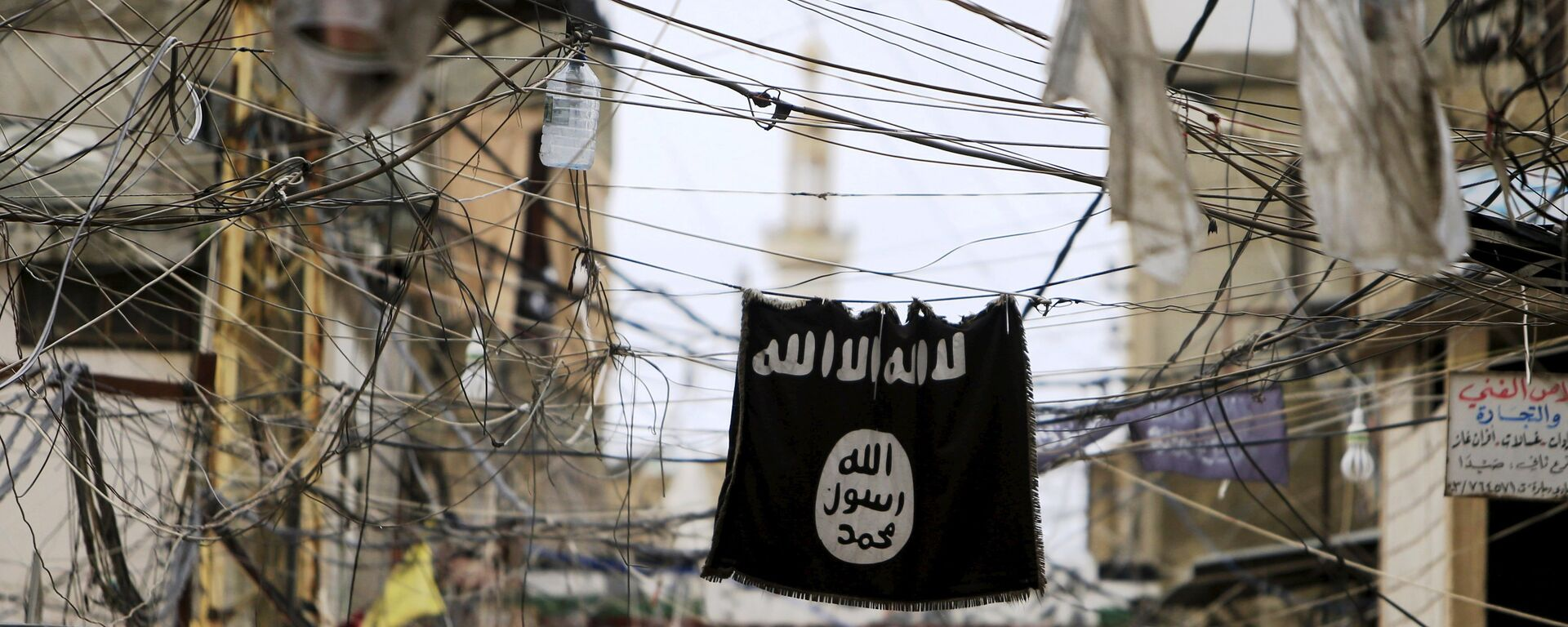 An Islamic State flag hangs amid electric wires over a street. - Sputnik International, 1920, 20.02.2021