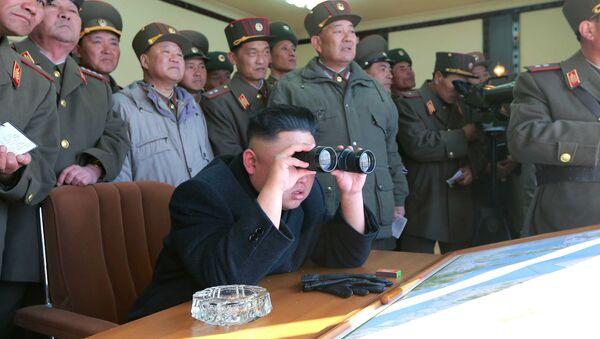 North Korean leader Kim Jong Un uses a pair of binoculars to watch live ammunition firing drills. - Sputnik International