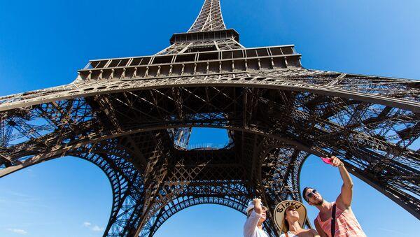 People taking a selfie in front of the Eiffel Tower, Paris. - Sputnik International