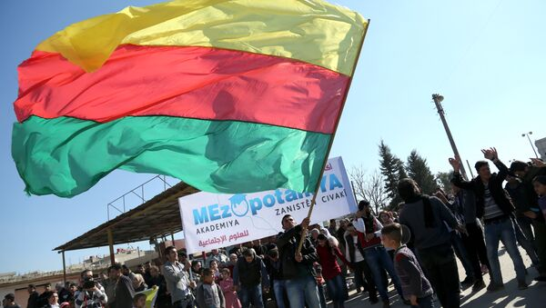 A Kurdish man waves a large flag of the Kurdish People's Protection Units (YPG) political wing, the Democratic Union Party (PYD), during a demonstration against the exclusion of Syrian-Kurds from the Geneva talks in the northeastern Syrian city of Qamishli on February 4, 2016 - Sputnik International