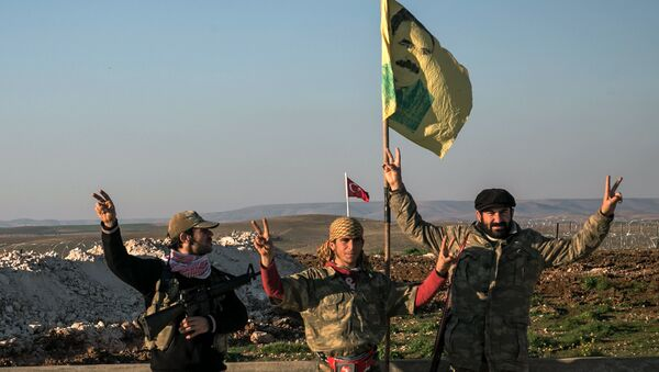 FILE - In this Sunday, Feb. 22, 2015, file photo, Syrian Kurdish militia members of YPG make a V-sign next to poster of Abdullah Ocalan, jailed Kurdish rebel leader, and a Turkish army tank in the background in Esme village in Aleppo province, Syria - Sputnik International