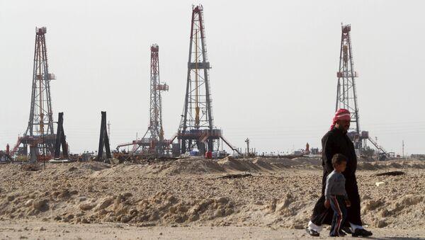 Iraqi people walk past the Rumaila oilfield in Basra, Iraq, January 26, 2016 - Sputnik International