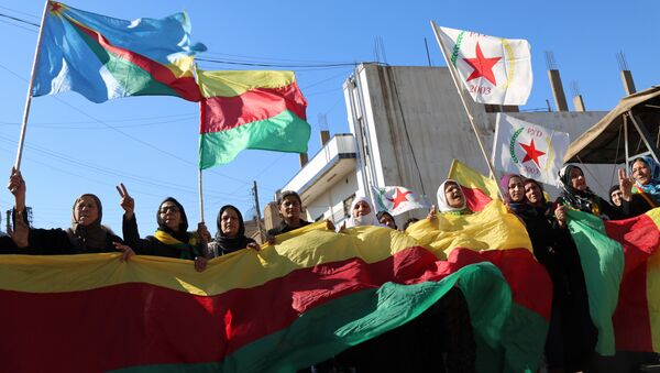 Kurdish women hold flags of the Kurdish People's Protection Units (YPG) political wing, the Democratic Union Party (PYD), and banners during a demonstration against the exclusion of Syrian-Kurds from the Geneva talks in the northeastern Syrian city of Qamishli on February 4, 2016 - Sputnik International