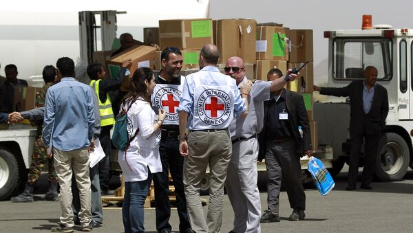Workers from the International Committee of the Red Cross (ICRC) stand on the tarmac as emergency medical aid from the ICRC is offloaded off a plane following its arrival at the international airport in Sanaa on April 10, 2015 - Sputnik International