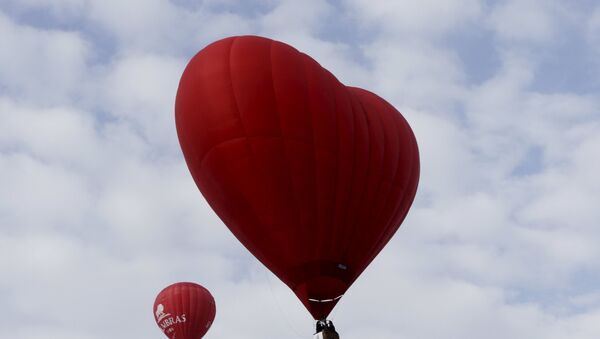 A heart-shaped hot air balloon (R) flies in the sky during the Love Cup 2016 event, ahead of Valentine's Day, in Jekabpils, Latvia, February 13, 2016 - Sputnik International
