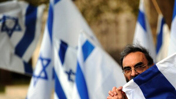 A man holds an Israeli fag during a counter demonstration against a nearby protest opposite Downing Street in central London, on October 6, 2011. - Sputnik International
