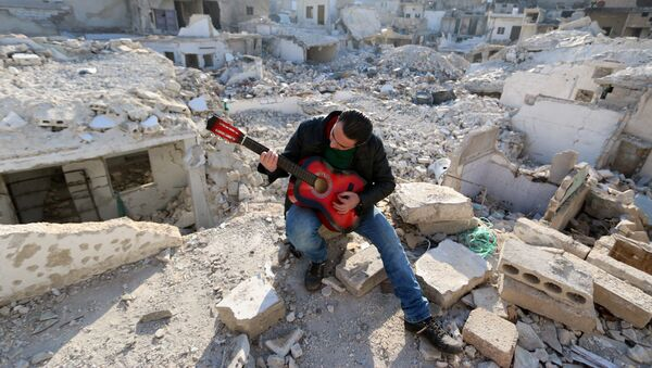 Shehab, a 23-year-old Syrian, practices the guitar amidst the rubble of buildings in the northern Syrian city of Aleppo on December 11, 2015. - Sputnik International