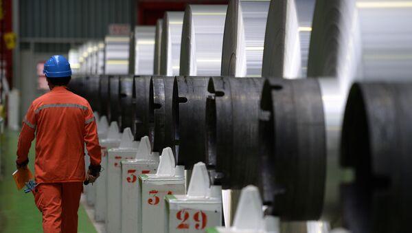 An employee walks along aluminium rolls at the Constellium factory, on December 12, 2014 in Biesheim, eastern France. - Sputnik International
