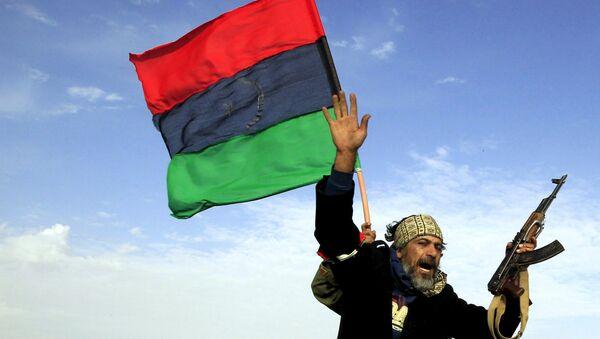 A rebel soldier gestures atop a car as he heads to Brega, in Ajdabiya March 2, 2011. - Sputnik International