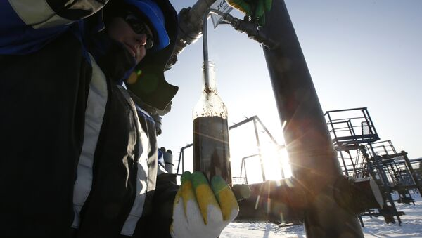 A worker takes oil samples from a well at the Gazpromneft company owned Yuzhno-Priobskoye oil field outside the West Siberian city of Khanty-Mansiysk, Russia, January 28, 2016 - Sputnik International