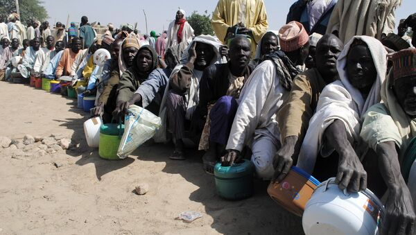 Internally Displaced Persons (IDP) mostly men sit in line waiting to be served with food at Dikwa Camp, in Borno State in north-eastern Nigeria, on February 2, 2016 - Sputnik International