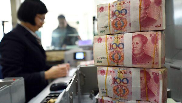 An employee counts 100-yuan (15 USD) banknotes at a bank in Lianyungang, in eastern China's Jiangsu province on January 7, 2016 - Sputnik International