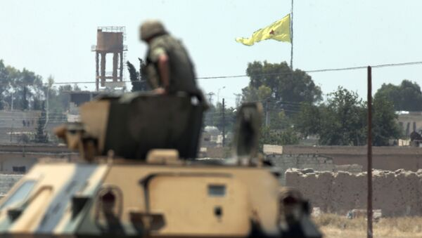 In this photo taken from the Turkish side of the border between Turkey and Syria, in Akcakale, southeastern Turkey, a Turkish soldier on an armoured personnel carrier watches as in the background a flag of the Kurdish People's Protection Units, or YPG, is raised over the city of Tal Abyad, Syria, Tuesday, June 16, 2015 - Sputnik International