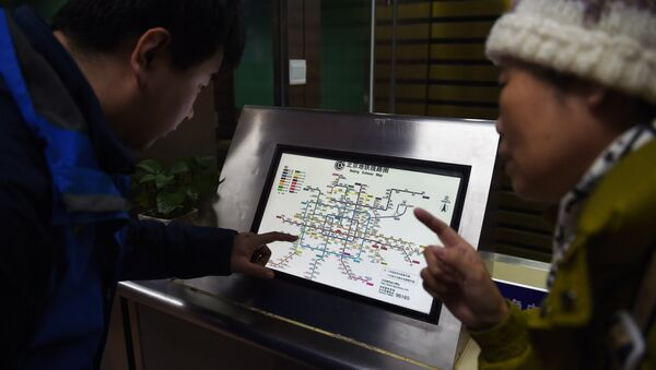 An attendant (L) explains details of new charges to a commuter in front of a subway map at a subway station in Beijing on December 29, 2014 - Sputnik International